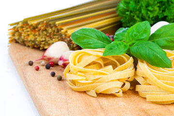 Italian pasta fettuccine nest with garlic and fresh basil leaves