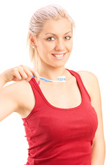 Woman holding a toothbrush and showing her shiny white teeth