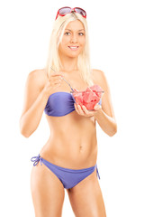 Attractive woman in bikini eating watermelon