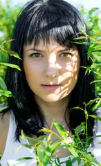 Beautiful girl in green foliage