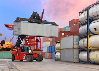 forklift handling the container box at dockyard with harbour bac