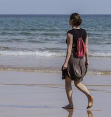 Chica con falda paseando por la orilla de la playa