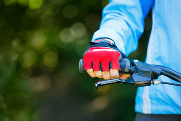 Closeup of hands in red protective gloves holding handlebar.