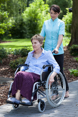 Nurse walking with disabled lady