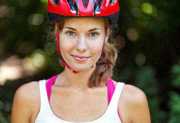 Portrait of happy young cyclist in sport clothes and helmet.