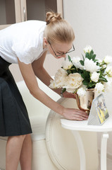 Young pretty business woman puts the vase with white peonies  on