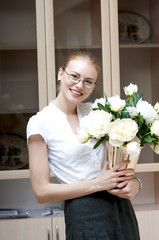 Happy smiling business woman holding a vase with white peonies.