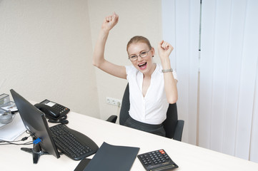 Business woman celebrating victory at the laptop computer.