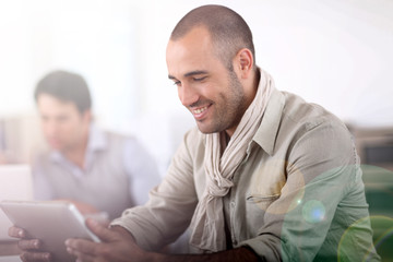 Smiling man in office using digital tablet
