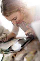 Young woman at work eating sandwich and using tablet