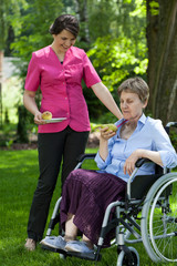 Disabled woman eating fruit in garden