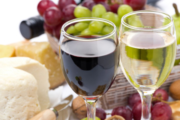 two glasses with white and red wine, cheese and grapes