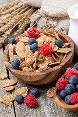 wholegrain flakes with fresh berries on wooden table, close-up