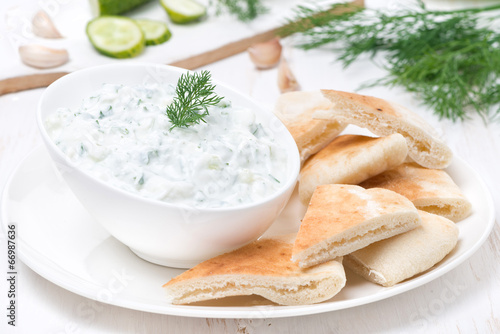 Fotobehang Kruiderij yoghurt sauce tzatziki with pieces of pita bread