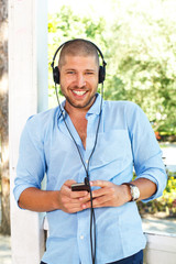 handsome guy in the light blue shirt posing with headphones and
