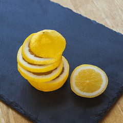 Lemon and lemon slices, juicy and ripe, on slate.