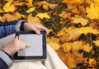 Teen uses a tablet in the autumn park