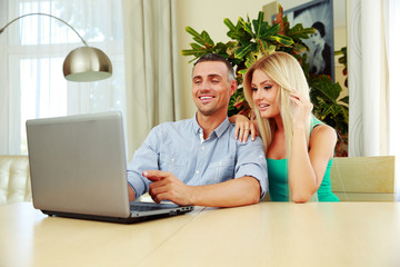 Cheerful couple using laptop together at home