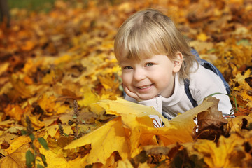 happy boy in leaves of autumn lies