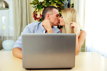 Young couple sitting at the table and kissing at home