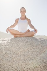 Smiling woman sitting in lotus pose on beach