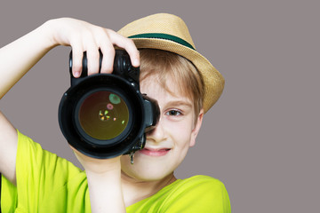 Young photographer with a camera, gray background