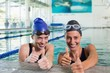 Female swimmers smiling at camera in the swimming pool