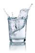 Leinwandbild Motiv Eiswürfel fällt in ein Glas mit Wasser
