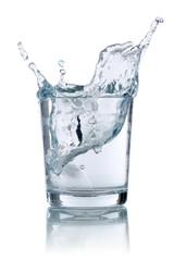 Eiswürfel fällt in ein Glas mit Wasser