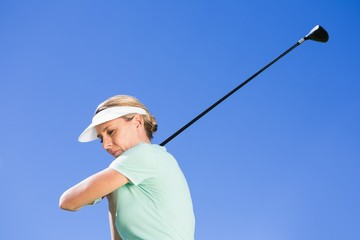 Female concentrating golfer taking a shot
