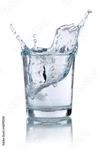 canvas print picture Eiswürfel fällt in ein Glas mit Wasser