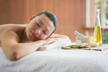 Brunette lying on massage table with tray of beauty treatments