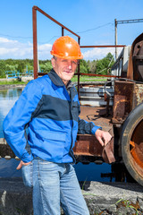 Senior man mechanist standing near sewage treatment plant