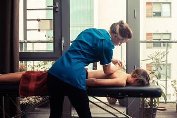 Massage therapist treating patient