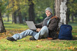 Young man working on laptop seated by a tree in park