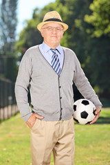 Senior gentleman holding a soccer ball in a park