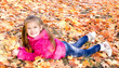 Autumn portrait of cute smiling little girl lying in maple leave