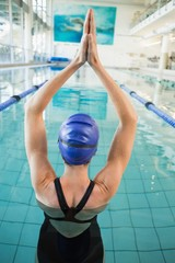 Fit swimmer in the pool with arms raised
