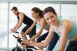 Fit people in a spin class with brunette smiling at camera