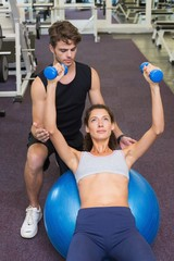 Trainer watching client lying on exercise ball with dumbbells