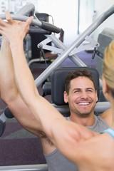 Personal trainer coaching bodybuilder using weight machine