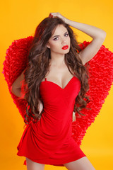 Beautiful female angel model posing with red wings in dress isol