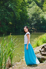 pretty woman wearing blue skirt posing in nature