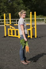Horse trainer standing holding a bunch of carrots