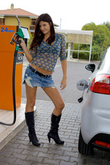 Happy sexy woman ready to put gas in car