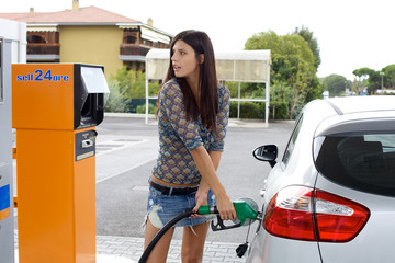 Happy woman pumping gas in car