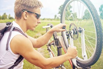 Cyclist checks wheel of bicycle