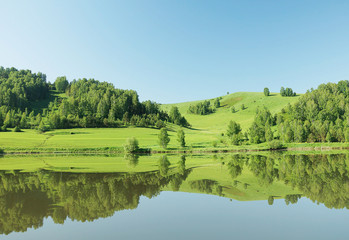 Beautiful summer landscape with green hills reflected in the cal