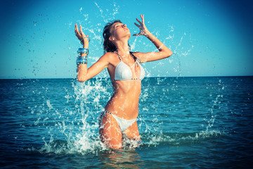 Beautiful woman jumps out of the sea  big splash