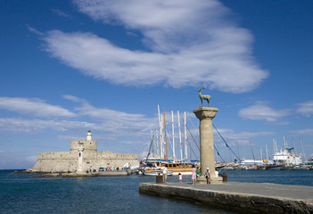 Rhodes Mandraki harbor with castle and famous deer statues